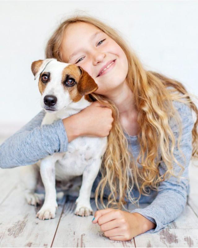 Smiling girl hugging a dog