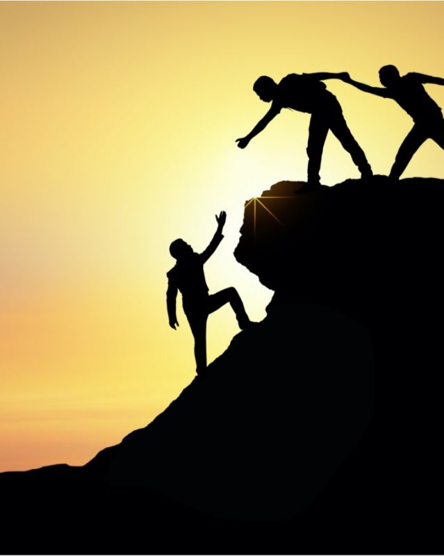 Two people helping another person climb a cliff